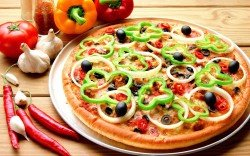 Pizza on metal dish and vegetable
