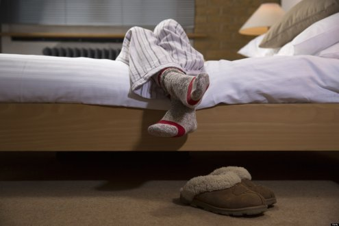 womans legs wearing pyjamas hanging off bed